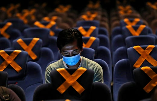 A man checks his mobile phone as he sits amid physical distancing markers prior to the start of a movie at CGV Cinemas theater in Jakarta, Indonesia, Friday, Oct. 23, 2020. The cinema reopened this week after months of closure due to coronavirus outbreak.
