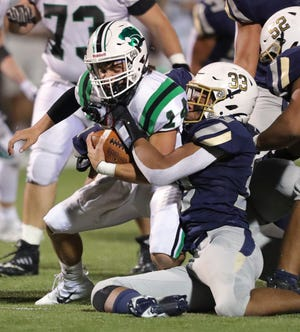 Hoban defensive end Chances Carter-Hill, right, sacks Mayfield quarterback Michael Huss during the first half of a Division II playoff football game at Dowed Field, Friday, Oct. 23, 2020, in Akron, Ohio. [Jeff Lange/Beacon Journal]