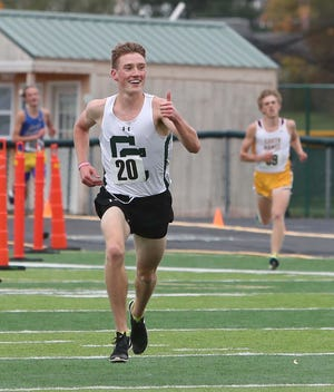 Barrett Scheatzle of Central Catholic gives a thumbs up as he approaches the finish line to win Division III boys race during Saturday's district cross country meet at GlenOak.