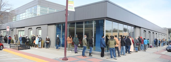 Story County voters wait in a line to cast their vote in the cold weather during early voting in front of Ames Public Library Saturday morning, Oct. 24, 2020, in Ames, Iowa. The library has recently gotten rid of its fines for materials returned late.