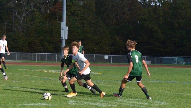 Life Center senior midfielder Hunter Bell (center) races Seneca's Matt Miller to a loose ball during Friday's nonleague soccer game.