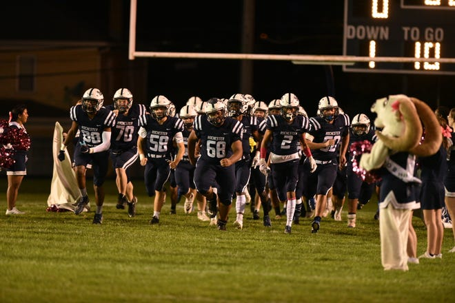 The Rochester football team runs onto the field minutes before their game against Shenango is held up Friday night due to an active shooter situation nearby.