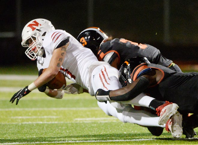 Beaver Falls' Mekhi Clark and Shileak Livingston tackle Neshannock's Cam'ron Owens during Friday night's game at Geneva College. The Tigers dominated the Lancers with a 46-27 victory.