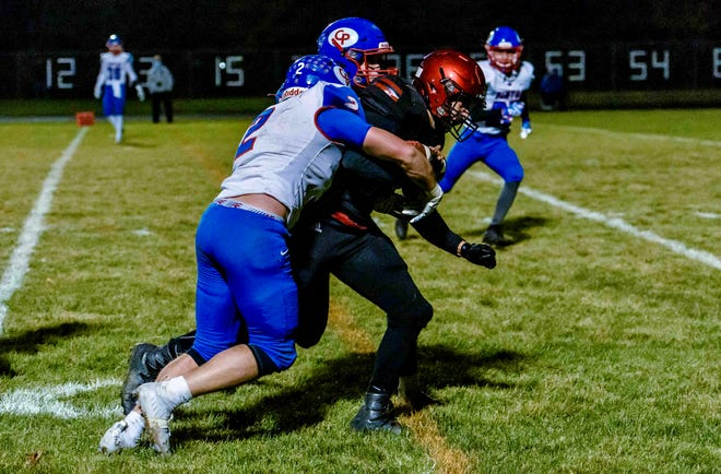 Southern Boone's Blake Dapkus (15) carries a pair of California defenders for extra yardage during a game Friday night at Southern Boone High School.