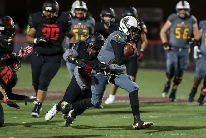 Battle's Khaleel Dampier (13) runs the ball as Hannibal's DaRell Perry (6) tries to tackle him during a game Friday night at Hannibal High School.