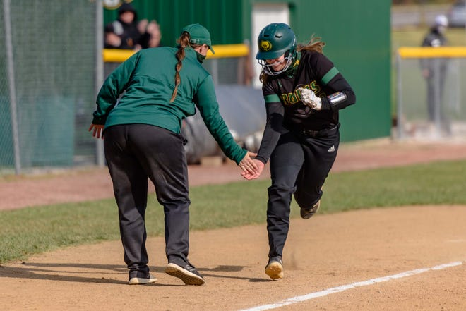 Rock Bridge head coach Lisa Simmons-Alvis, left, slaps hands with Abby Hay (23) as she rounds third base after her two-run home run to put Rock Bridge ahead for good during a Class 5 semifinal game against Marquette on Saturday at Rock Bridge High School.