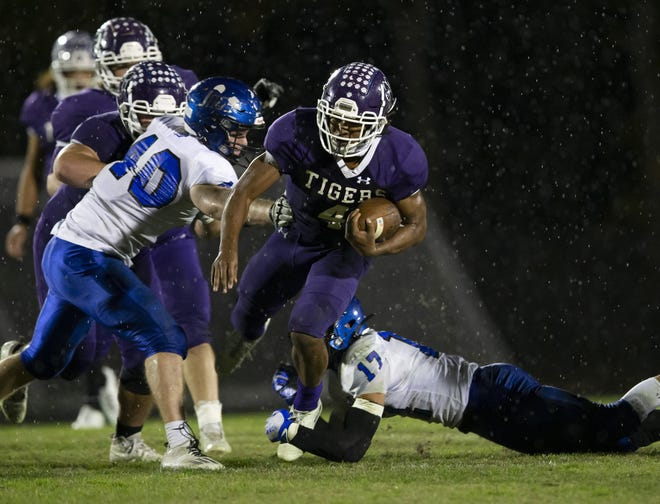 Pickerington Central running back Nick Mosley runs through Hilliard Bradley defensive end Max Cooper (17) and linebacker Ibrahim Musa (40) during a Division I regional semifinal in Pickerington on Friday.