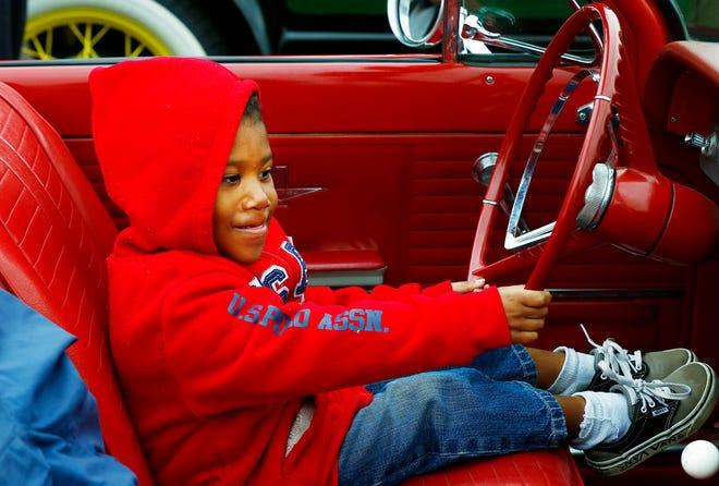 Deshaun Bennett, 4, hops behind the wheel of Lee Laubacher's 1964 Corvair during the inaugural Orr Park Fall Festival Saturday.