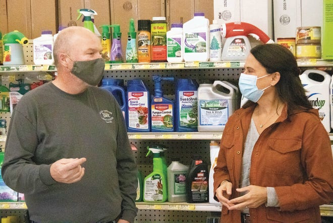 Owner Geoff Warmouth talks to Democratic U.S. Senate Candidate Theresa Greenfield during a visit to Waukee Hardware and Rent-It Center on Saturday, Oct. 24.