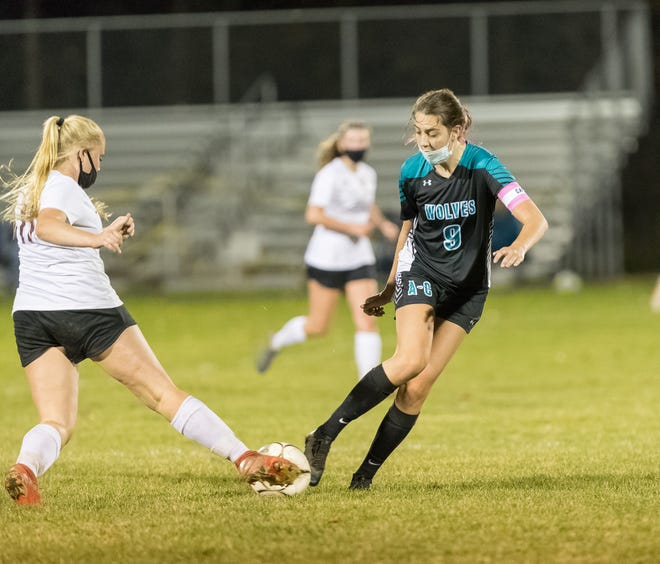 Arkport/Canaseraga's Julia Flaitz (9) looks to take the ball away from Addison Friday night.