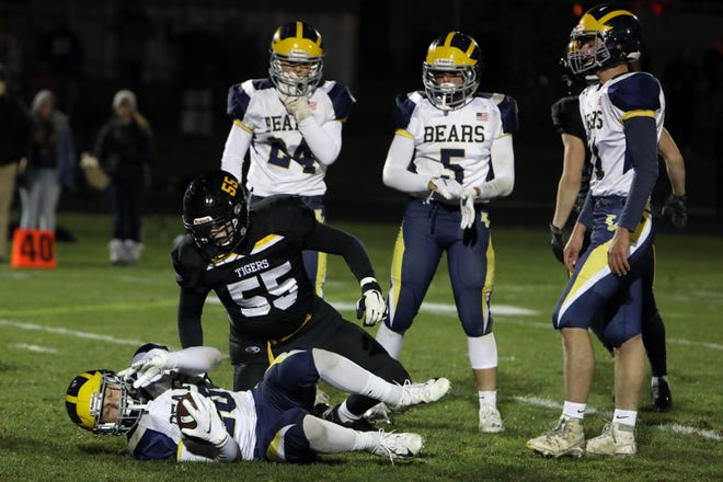 New London High School's Carter Allen (55) gets up after tackling Beau Flander (20) during the first half of their Class 8-Man second round playoff game against the English Valleys Bears, Friday Oct. 23, 2020 at New London.