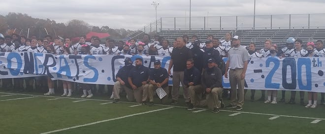 North Penn players, coaches  and cheerleaders help head coach Dick Beck (center) celebrate his 200th career coaching win Saturday.