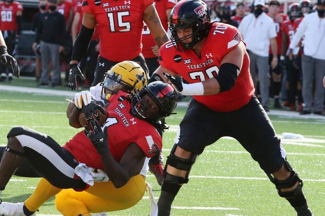 West Virginia linebacker Josh Chandler-Semedo, left, tackles Texas Tech running back SaRodorick Thompson during the Red Raiders' 34-27 victory Saturday at Jones AT&T Stadium. Thompson left the game in the third quarter with an upper-body injury and did not return.