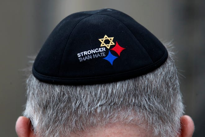 """A man wearing a """"Stronger Than Hate"""" yarmulke stands outside the Tree of Life synagogue in Pittsburgh in October 2019, on the first anniversary of the shooting at the synagogue, that killed 11 worshippers. On Tuesday, Oct. 27, 2020, as they again mourn those killed two years earlier, they'll also celebrate the resilience that has enabled them to persevere."""