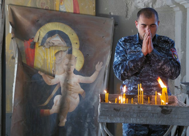 A policeman prays Saturday in the Holy Savior Cathedral, damaged by shelling by Azerbaijan's artillery during a military conflict in Shushi, the separatist region of Nagorno-Karabakh with a damaged icon of the Virgin on the left.
