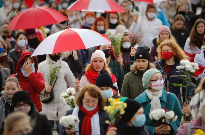 Belarusian women with umbrellas in the colors of the old Belarusian national flag take part in an opposition rally to protest the official presidential election results in Minsk, Belarus, on Saturday. Several hundred women have marched under heavy rain across the Belarusian capital to demand the resignation of the country's authoritarian president.