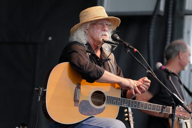 Arlo Guthrie talks during an Aug. 15 concert at a Woodstock 50th anniversary event in Bethel, N.Y. In lengthy posts on his Facebook page and website, the 73-year-old folksinger announced Friday he is retiring from performance immediately. He's canceled numerous shows next year and says he won't book any new ones.