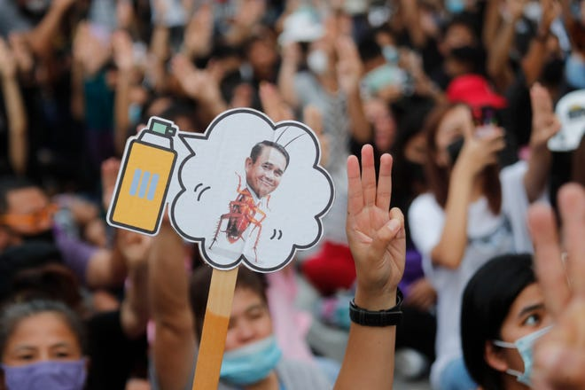 Pro-democracy activists display a placard with Thai Prime Minister Prayuth Chan-ocha's head attached to a cockroach during a protest outside remand prison, in which some of the activists are kept, in Bangkok, Thailand, on Friday. Thailand's government on Thursday canceled a state of emergency it had declared last week for Bangkok in a gesture offered by the embattled prime minister to cool student-led protests seeking democracy reforms.