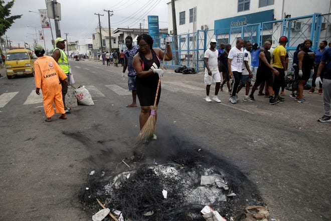 """Volunteers sweep burnt out tires on the roads in Lagos on Saturday. Nigeria's president said 51 civilians have been killed in unrest following days of peaceful protests over police abuses, and he blames """"hooliganism"""" for the violence while asserting that security forces have used """"extreme restraint."""""""