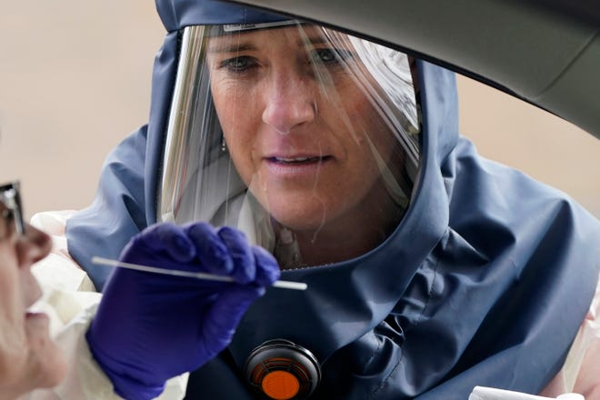 """Salt Lake County Health Department public health nurse Lee Cherie Booth performs a coronavirus test outside the Salt Lake County Health Department on Friday in Salt Lake City. Utah hit another ominous record by tallying the highest number of confirmed coronavirus cases in a single day as the state struggles to slow a monthlong surge of COVID-19 that is filling intensive care beds at hospitals. Gov. Gary Herbert warned in a statement that the state is """"on the brink,"""" and once again pleaded with people to adhere to mask mandates in place in most counties in the state."""