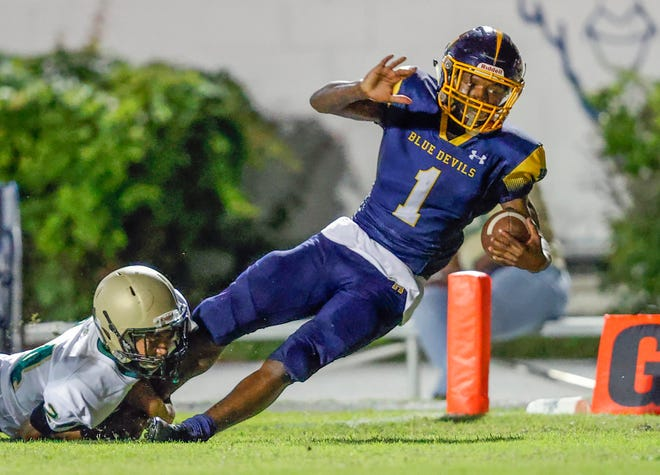 Winter Haven's Jakobe Lane drags George Jenkins defender Jamar Wiggins into the end zone as he scores during the high school football game at Denison Stadium in Winter Haven on Friday.