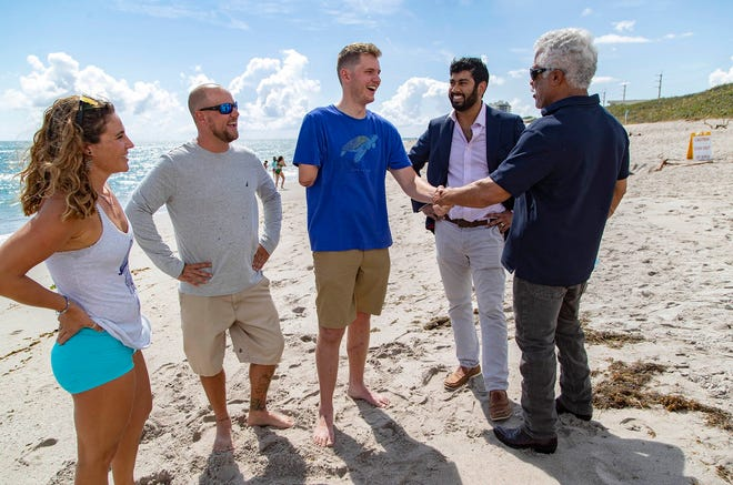 Palm Beach Post staff writer Joe Capozzi won the trust of Carter Viss and those who helped save him, helping to bring them all together on the beach 10 months after they saved Viss' life after he was hit by a boat. From left to right, Christine Raininger, Andy Earl, Carter Viss, Dr. Dilhan Abeyewardene and Dr. Robert Borrego.
