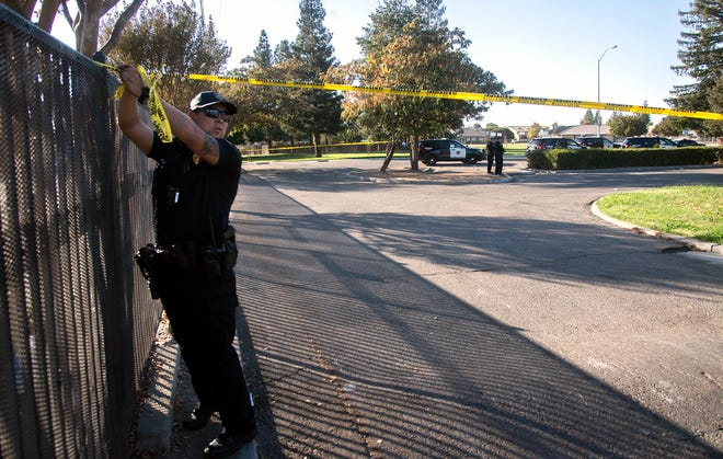 A Stockton police officers puts up crime scene tape to cordon off the scene of a shooting in the parking lot of the skate park at Anderson Park in Stockton on Friday afternoon that left a 21-year-old male injured.