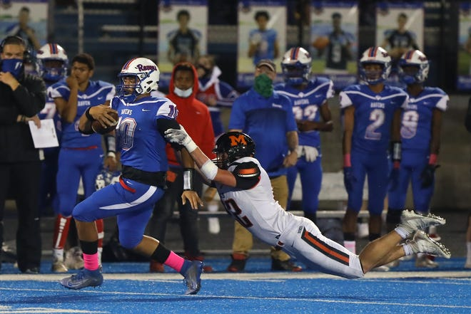 Ravenna junior quarterback Eathan Cobbin eludes Marlington junior defender Sam Dine during Friday night's game at Ravenna High School.