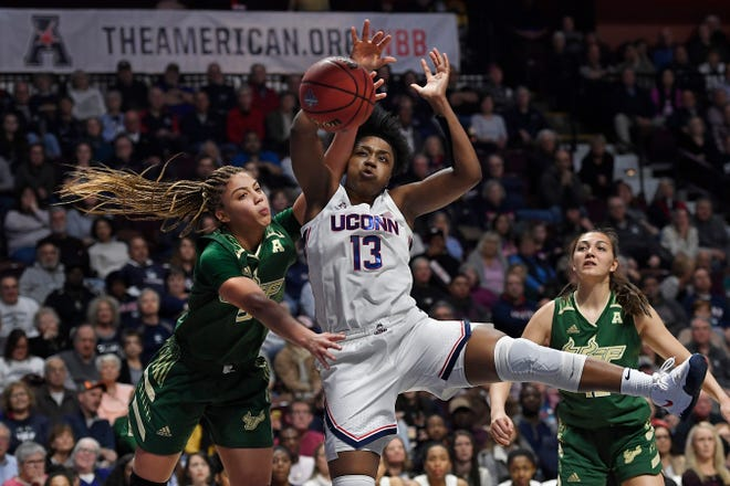 South Florida's Elena Tsineke, left, fouls Connecticut's Christyn Williams (13) during last season's AAC tournament at Mohegan Sun Arena in Uncasville.