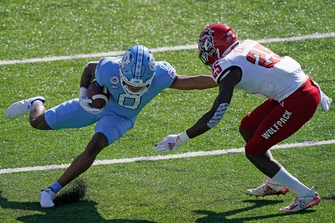 North Carolina wide receiver Emery Simmons (0) runs the ball after catching a pass while North Carolina State cornerback Shyheim Battle (25) looks to tackle during Saturday's game. [Gerry Broome/The Associated Press]