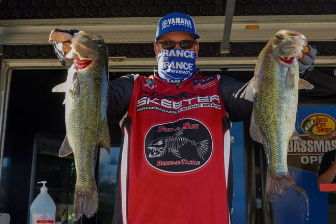 Cody Bird holds up two of his catch Friday after the second round of the Bassmaster event on Neely Henry Lake in Gadsden. Bird currently leads the event heading into Saturday's final day.