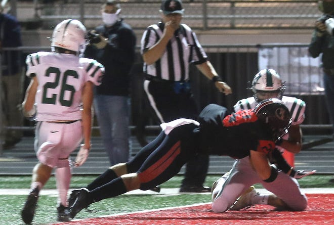 New Philadelphia's Logan Ortt dives into the end zone for the first touchdown in the Division III playoff game with Aurora Friday.