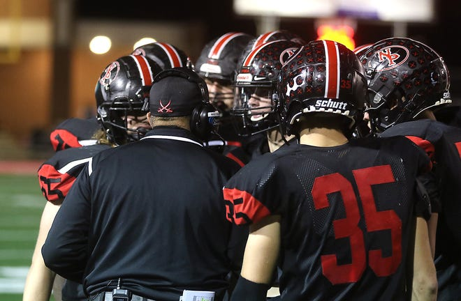 The New Philadelphia Quakers talk strategy during a Division III regional playoff game with Aurora at Woody Hayes Quaker Stadium this past season.