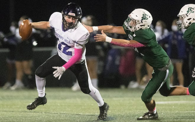 Cherry Hill West's Nick Arcaroli, left, runs the ball past Camden Catholic's Dan Dever during the 1st quarter of the football game played at Camden Catholic High School on Friday, October 23, 2020.