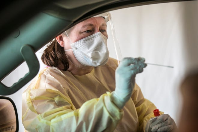 Mary Harney, RN, conducts a COVID-19 test at the drive-thru testing site at Mercy Health Anderson Hospital, Thursday, Oct. 22, 2020. If you're symptomatic, you get the test via the throat. If you're having a procedure, it's in the nose. They're open from 8am - 1pm and do about 70 tests each day. Over 5,000 deaths in Ohio have been reported during the pandemic, according to Ohio Department of Health.