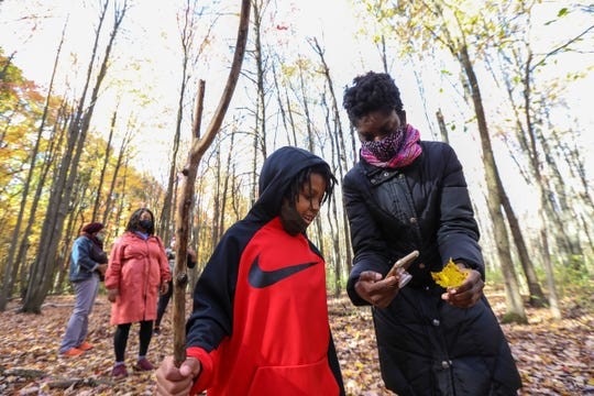 Noah Ferguson, 7, of Detroit, identifies maple tree using a leaf and an application on Jalyn Spencer-Harris' phone during a nature walk with members of Detroit Mama Hub meet up at Bauervic Woods Park in Southfield, Mich. on Oct. 24, 2020. Detroit Mama Hub's mission is to improve the well-being of mothers through accessible, high-quality lactation and postpartum support so that mothers and their families can thrive.