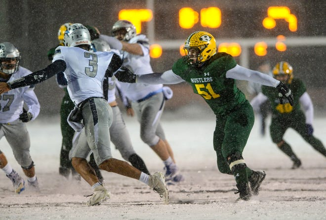 C.M. Russell lineman Tyler Marr (51, right) tries to chase down Great Falls High quarterback Reed Harris (3) during last Friday's Crosstown Game at Memorial Stadium, won by the Bison 35-7.
