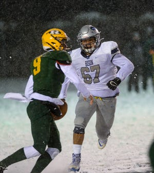 Great Falls High's Ethan DeRoche attempts to chase down CMR quarterback Raef Newbrough during the crosstown football game on Friday.