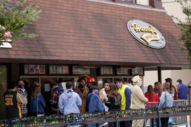 Bar-goers line up outside Harry's Chocolate Shop before Purdue University's football game against Iowa, Saturday, Oct. 24, 2020 in West Lafayette.