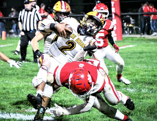 Berne Union junior Brae Friesner fights to stay upright as he is being tackled by a Trimble defender Friday night  in Glouster.  Trimble won 35-14.