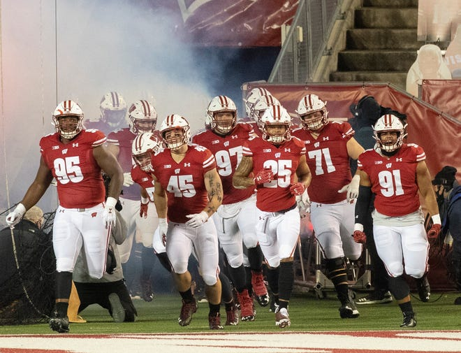 With only cardboard cutouts in the stands, the Wisconsin football team takes to the field for their season opener Friday at Camp Randall Stadium.