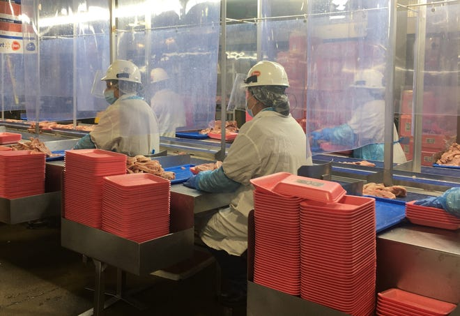 """Plastic sheeting separates employee work stations to prevent the spread of coronavirus at the Tyson Foods meatpacking facility in Goodlettsville, the site of a 280-person cluster in April. City officials say the Tyson cluster was a """"kickoff"""" for the virus spreading through much of the city's essential workforce."""