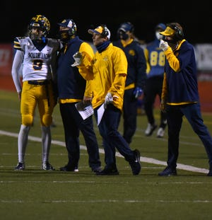 South Lyon quarterback Dawson Skupin, left, huddles with his coaches near the sideline.