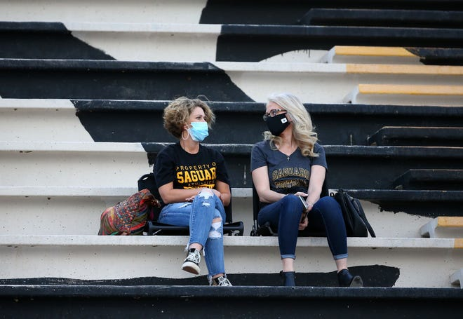 Saguaro Sabercats fans wear masks during a national televised game against Hamilton Huskies at Saguaro High School.