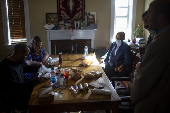 Neko Wilson (left) prays with his fiancé Cassandra Sabatino (back left), his older brother Jacque Wilson (back right), his defense attorney Lee Phillips (center right) and his older brother Jacq Wilson (front right) before eating his first meal after being released from Navajo Country Jail at Phillips' law office in Flagstaff, Ariz. on Oct. 23, 2020.
