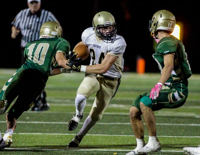 Delone Catholic running back Tate Neiderer breaks a tackle by York Catholic defensive back Quinn Brennan, Friday, October 23, 2020John A. Pavoncello photo