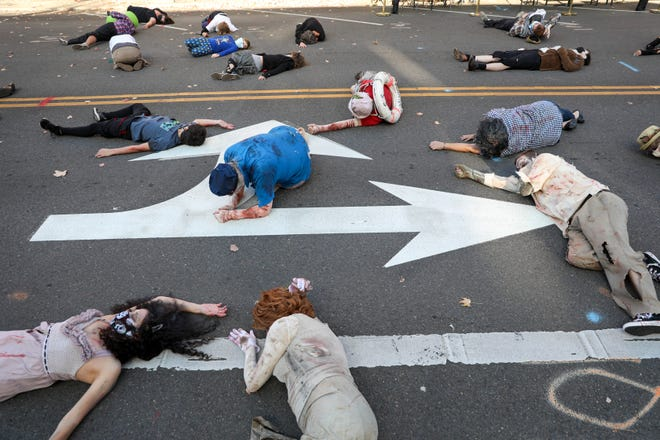 "Dancers lay on the ground at the start of the annual Thrill the World dance Saturday outside of Taproot Lounge in Salem. Participants gathered to do the zombie dance from Michael Jackson's ""Thriller"" with other groups simultaneously around the globe."