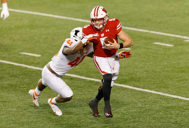Wisconsin quarterback Graham Mertz is tackled by Illinois linebacker Tarique Barnes during the second quarter at Camp Randall Stadium.