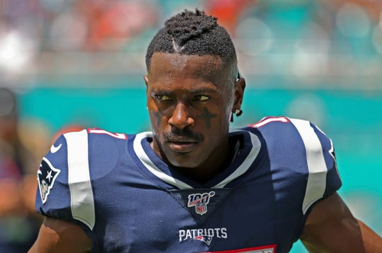 In this Sunday, Sept. 15, 2019, photo, New England Patriots wide receiver Antonio Brown waits for the team's NFL football game against the Miami Dolphins to begin in Miami Gardens, Fla.