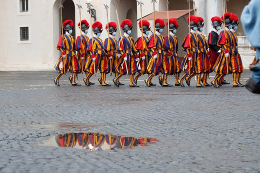 Vatican Swiss Guards wearing masks to curb the spread of COVID-19 march as they leave the St. Damaso courtyard after the visit of Spain's Prime Minister Pedro Sanchez to Pope Francis, at the Vatican, Saturday, Oct. 24, 2020.